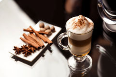 Latte macchiato with spices. Latte macchiato spices on white plate (cinnamon, anise star and nutmeg Stock Images