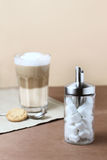 Latte macchiato with sugar dispenser Royalty Free Stock Photography