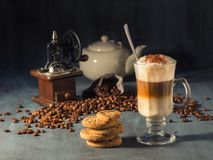 Latte macchiato in a tall glass with chocolate sprinkles. In the background there are spilled coffee beans and a coffee grinder royalty free stock images