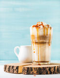 Latte macchiato with whipped cream and caramel sauce in tall glass on wooden board over blue painted wall background Stock Photo