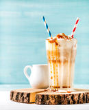 Latte macchiato with whipped cream and caramel sauce in tall glass on wooden board over blue painted wall background Royalty Free Stock Photography