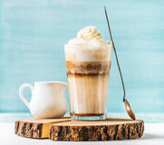 Latte macchiato with whipped cream, serving silver spoon and pitcher on wooden round board over blue painted wall Stock Photos