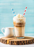 Latte macchiato with whipped cream in tall glass and pitcher on round wooden board over blue painted wall background Royalty Free Stock Photos