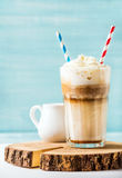 Latte macchiato with whipped cream in tall glass , two straws and pitcher on wooden board over blue painted wall Royalty Free Stock Photo