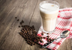 Latte macchiato. On a wooden table with coffee beans royalty free stock images