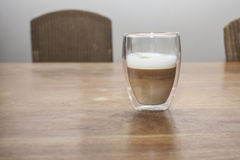 Latte Machiato. A glass with a latte machiato on a wooden table Royalty Free Stock Photography