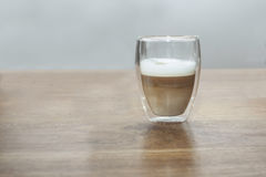 Latte Machiato. A glass with a latte machiato on a wooden table Stock Images