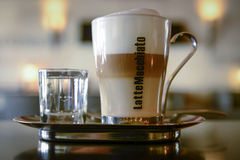 Latte machiato served with water. A glass of coffee and water on a silver plate Stock Photo