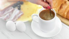 Latte mescolantesi della mano femminile del primo piano in tazza di caffè facendo uso dell'angolo alto del cucchiaio stock footage