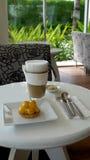 Latte mit Kuchen auf Tabelle Stockfotos