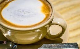 Latte mit schaumigem Schaum, Sonnenbräunebecher, Seitenansicht lizenzfreie stockbilder