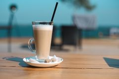 Latte mug with black drinking straw on wooden table.  stock photos