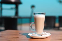 Latte mug on a wooden table with lump sugar.  stock image