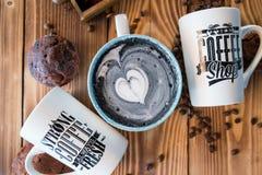 Latte negro con espuma negra del corazón en taza de cerámica del arte en el viejo tablero de madera, visión superior Fotografía de archivo