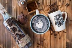 Latte negro con espuma negra del corazón en taza de cerámica del arte en el viejo tablero de madera, visión superior Imágenes de archivo libres de regalías