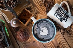 Latte negro con espuma negra del corazón en taza de cerámica del arte en el viejo tablero de madera, visión superior Fotos de archivo