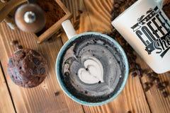 Latte negro con espuma negra del corazón en taza de cerámica del arte en el viejo tablero de madera, visión superior Imagenes de archivo
