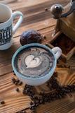 Latte negro con espuma negra del corazón en taza de cerámica del arte en el viejo tablero de madera, visión superior Fotografía de archivo libre de regalías
