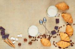 Latte o caffè caldo con latte decorato con i chicchi di caffè, i croissant, il cioccolato, le spezie ed i cucchiai dell'annata Fotografie Stock Libere da Diritti