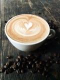 Latte- oder Cappuccinoschale auf hölzernem Schreibtisch Lizenzfreie Stockbilder