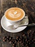 Latte- oder Cappuccinoschale auf hölzernem Schreibtisch Stockfotos