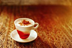 Latte per koppen p? en tr?tabell royaltyfria bilder