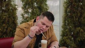 Latte potable d'homme sur la véranda à la table clips vidéos