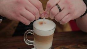 Latte potable d'homme sur la véranda à la table banque de vidéos