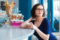 Latte potable de femme heureuse au compteur de barre en café images stock
