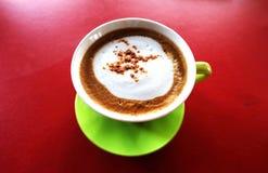 Latte quente do café no copo verde; fundo branco Foto de Stock