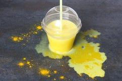 Latte rovesciato della curcuma sulla tavola scura Latte dorato versato sul tavolo da cucina Tazza di latte dorato fotografie stock libere da diritti