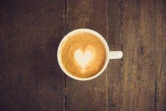 Latte sztuki kawa na drewno stole Zdjęcia Royalty Free