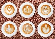 Latte sztuki kawa na piec kawowych fasoli tle obrazy royalty free