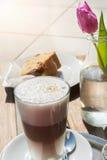 Latte, Torte und Blume auf einer Tabelle im Sonnenlicht Lizenzfreie Stockbilder