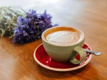 Latte on wooden desk with flower cornflower in retro film filter effect stock image