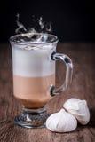 Lattecoffeexponeringsglas med bönor och maräng Arkivbild