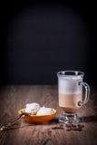 Lattecoffeexponeringsglas med bönor och maräng Arkivfoto