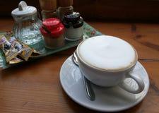 Lattekaffe på trätabellen Arkivbild