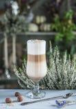 Lattekastanie in einem schönen Glas und in einem antiken Löffel auf Tabelle auf dem Hintergrund von Heide stockbild