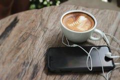 Lattekoffie in kop en slimme telefoons stock foto