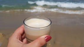 Lattekoffie in vrouwelijke hand tegen zeewaters stock fotografie