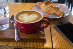 Lattekonstkaffe i röd kopp Arkivbilder