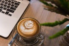 Lattekonstkaffe med bärbar datordatoren på trätabellen arkivbild
