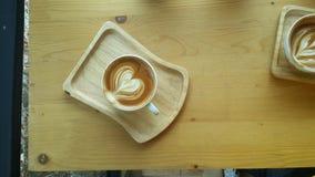 Lattekonstkaffe med hjärtasymbol på trätabellen Arkivbilder