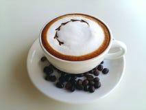 Lattekonstkaffe med kaffebönan som så är läcker på vit Arkivbilder