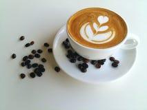Lattekonstkaffe med kaffebönan som så är läcker på vit Royaltyfri Bild