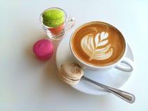 Lattekonstkaffe och makron som så är läckra på vit Royaltyfri Bild
