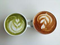 Lattekonstkaffe och matchalatte som så är läcker på vit Arkivfoton