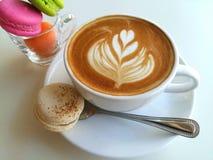Lattekonstkaffe som så är läckert med makron på vit Arkivbild