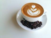 Lattekonstkaffe som så är läckert på trä Arkivfoto